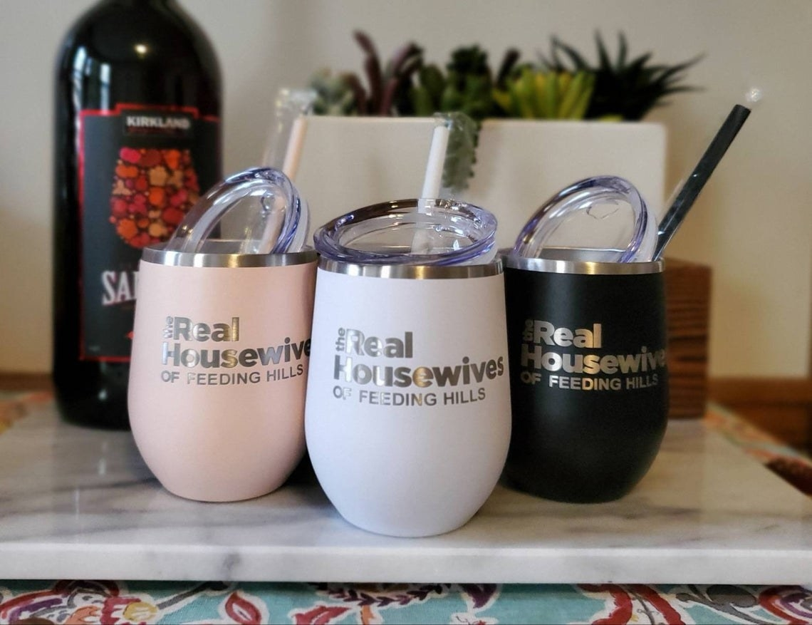"a light pink, white, and black set of stemless wine tumblers with ""Real Housewives of Feeding Hills"" in the style of the TV show font on a cutting board"