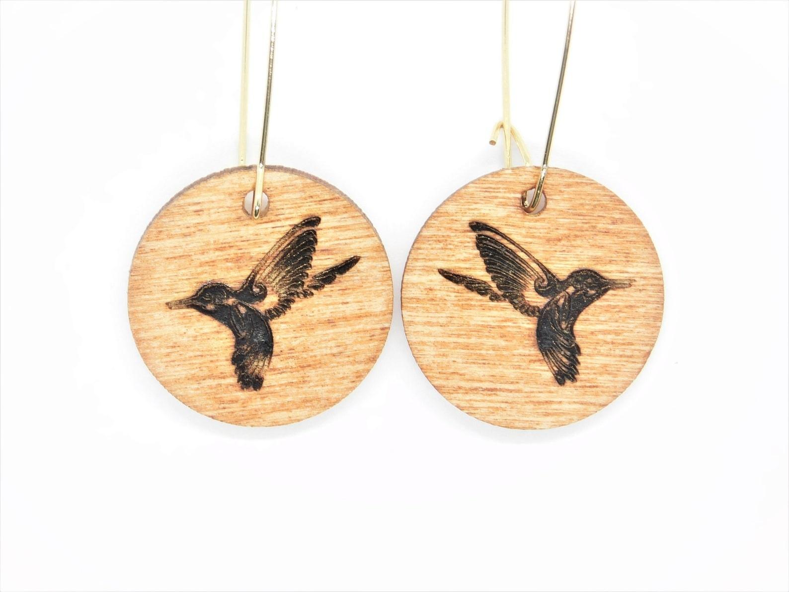 Closeup of two wooden hummingbird earrings
