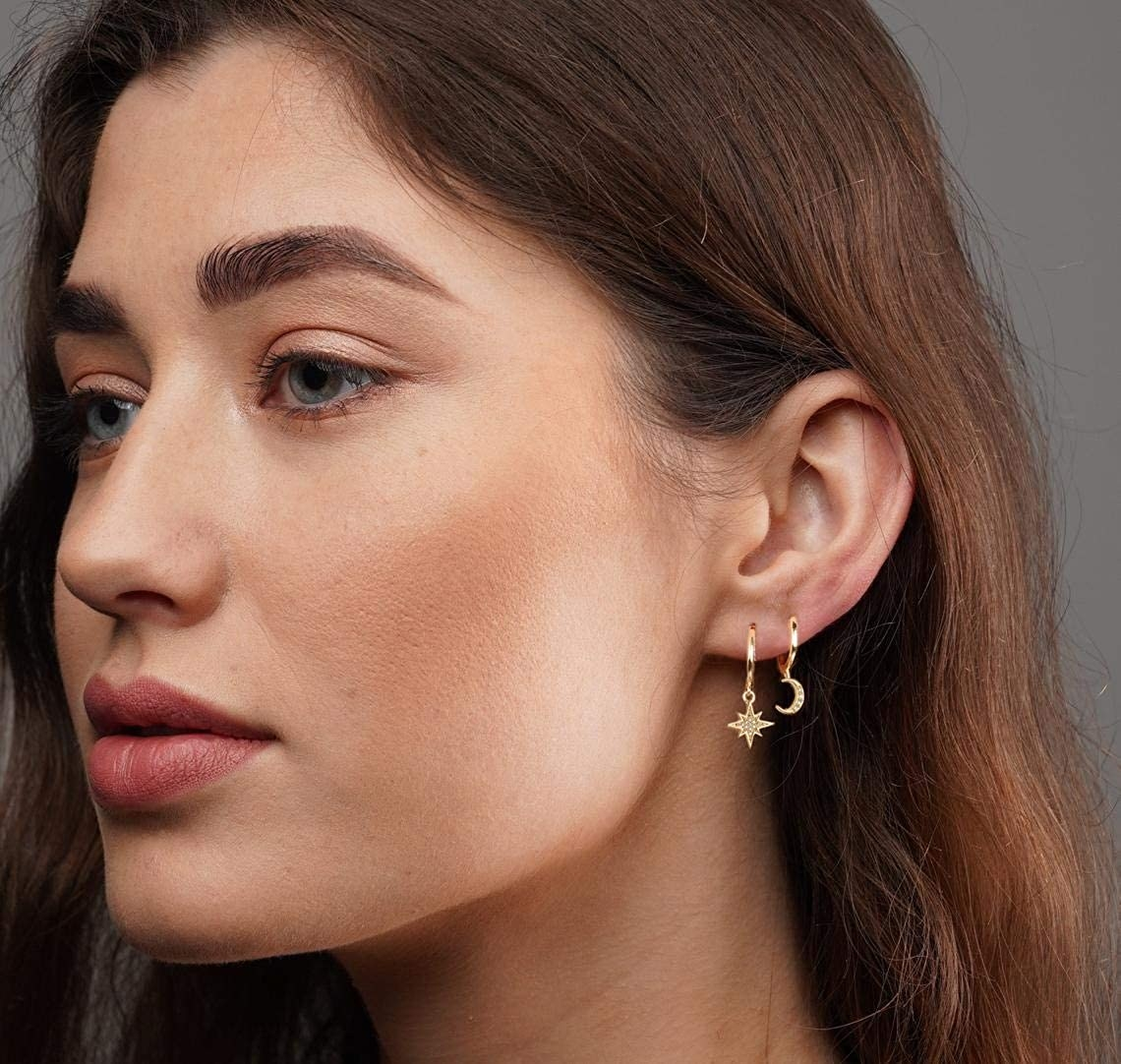 Model wearing star and moon-shaped earrings