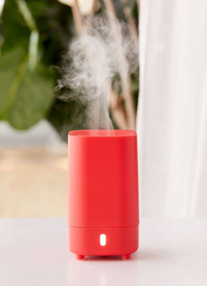 Red essential oil diffuser on top of a white table