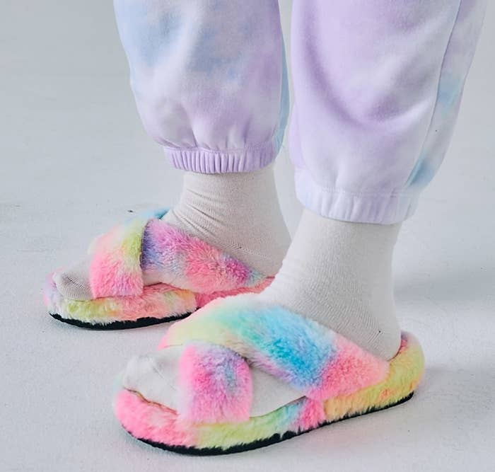Model wears criss-cross fluffy rainbow slippers with white socks and tie-dye pants
