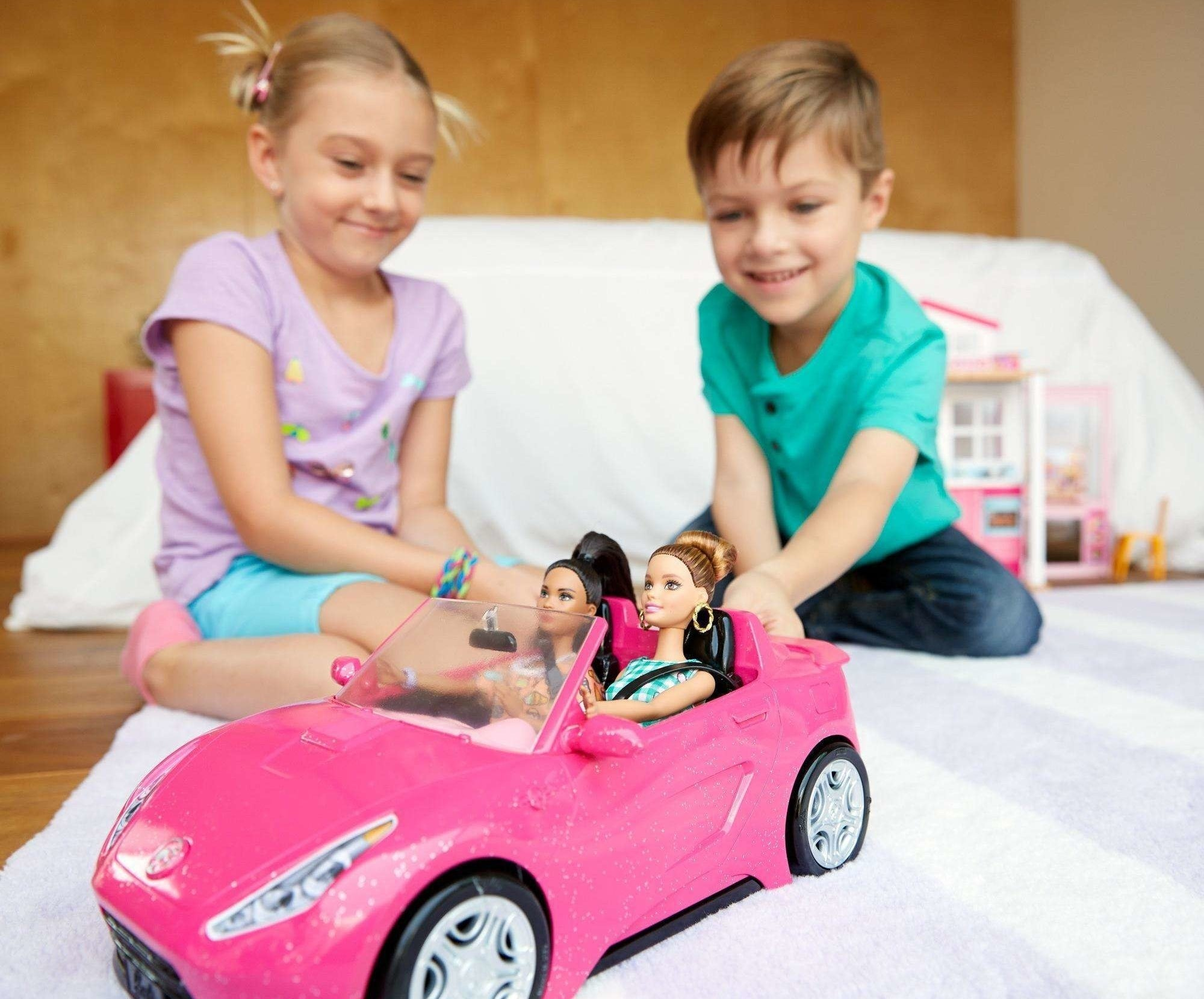 two children playing with a pink convertible car with barbie dolls in it