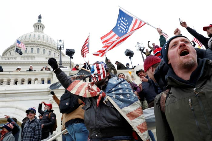 Rioters with American flags and at least one containing the Three Percenters symbol outside the Capitol