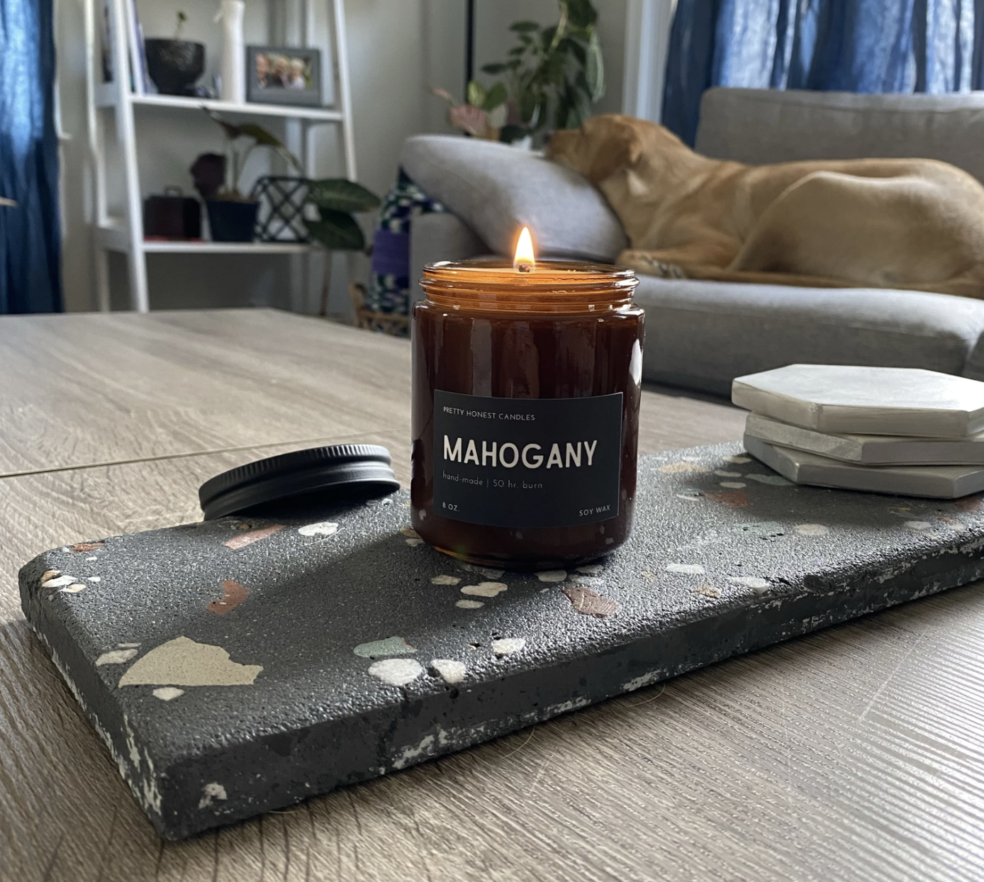 Mahogany soy candle on top of rectangular coaster in living room