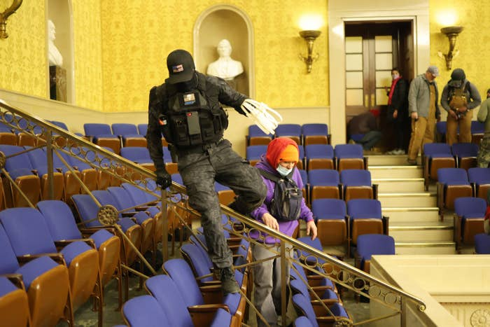 A man in tactical gear with a hat low over his head hops over a railing inside the Senate