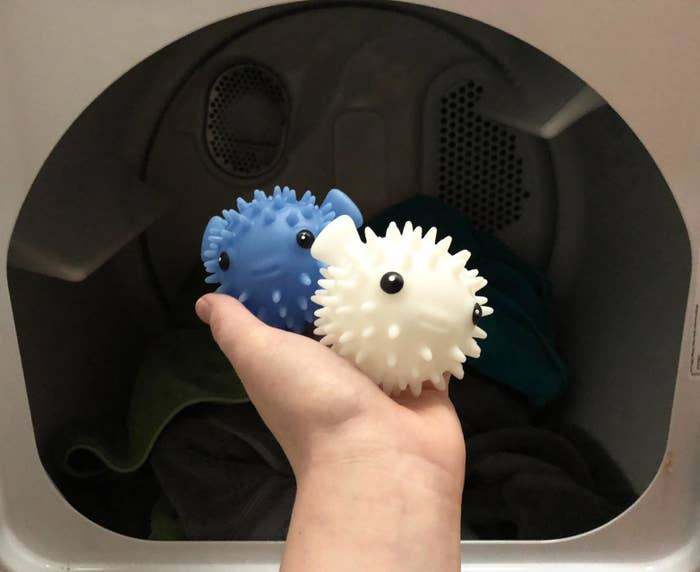 reviewer image of a customer holding the two kikkerland puffer fish drying buddies in front of their open dryer
