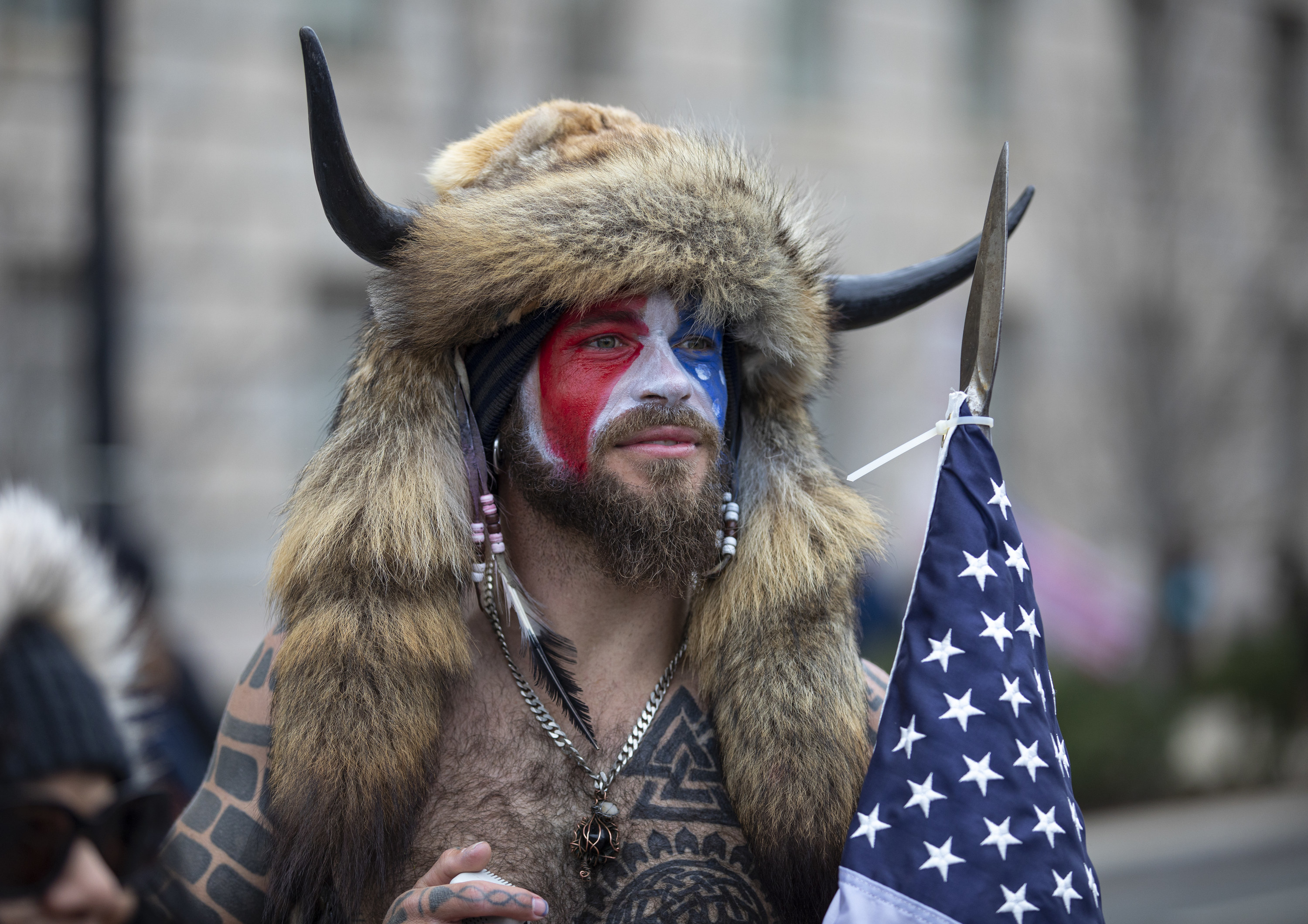 Chansley wearing a fur hat with horns and carrying an American flag with red, white, and blue face paint on
