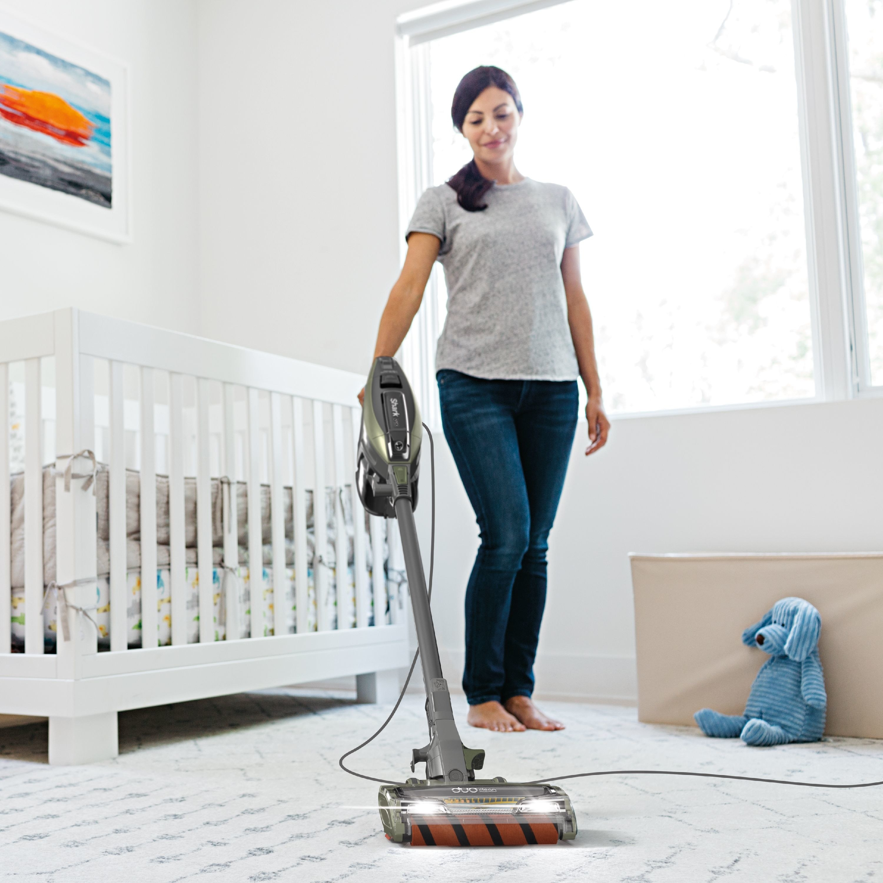 person using a corded stick vacuum to clean a rug