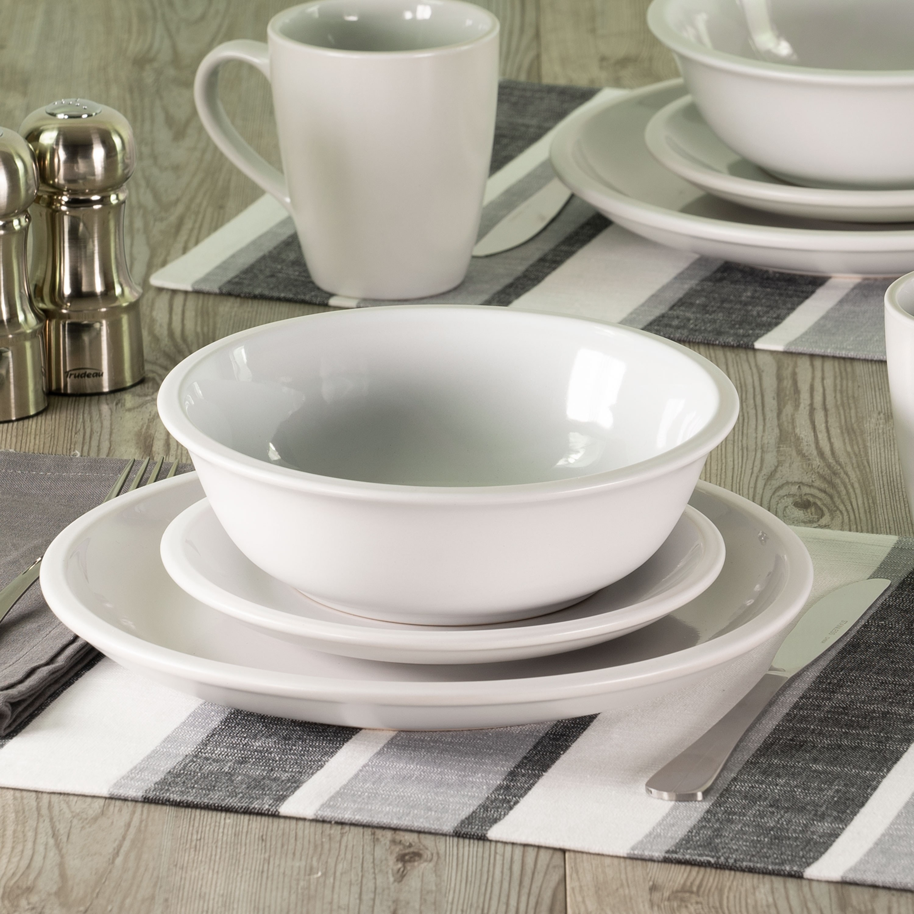 a white dinnerware set includes two plates, one bowl, and a mug