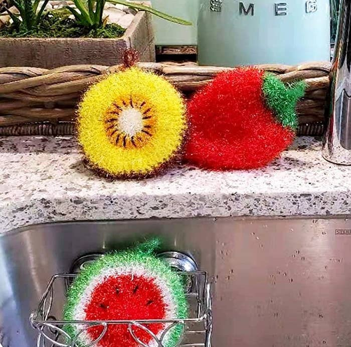 three hand crocheted fruit dish scrubbers by a kitchen sink
