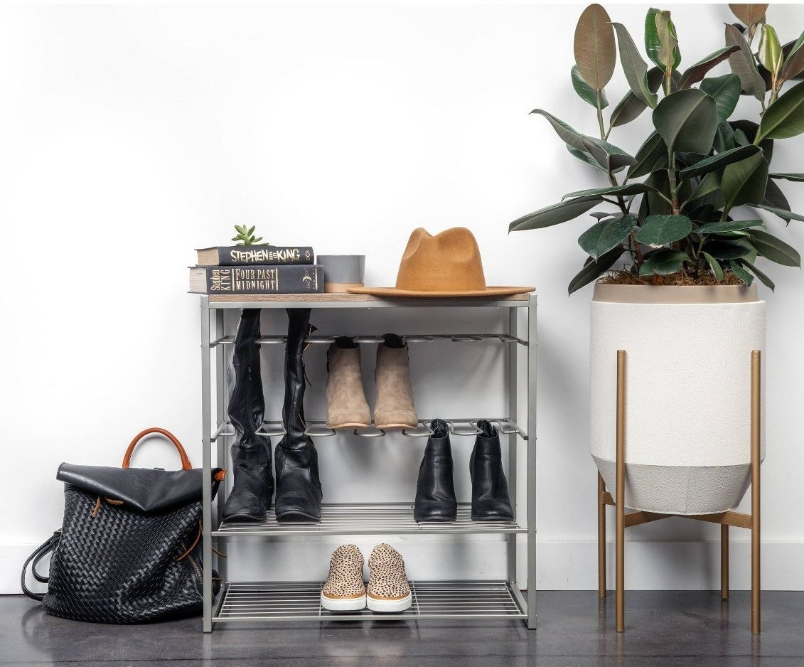 The four-tiered shoe shelf with tall and short shoes and a ledge to place other accessories on top