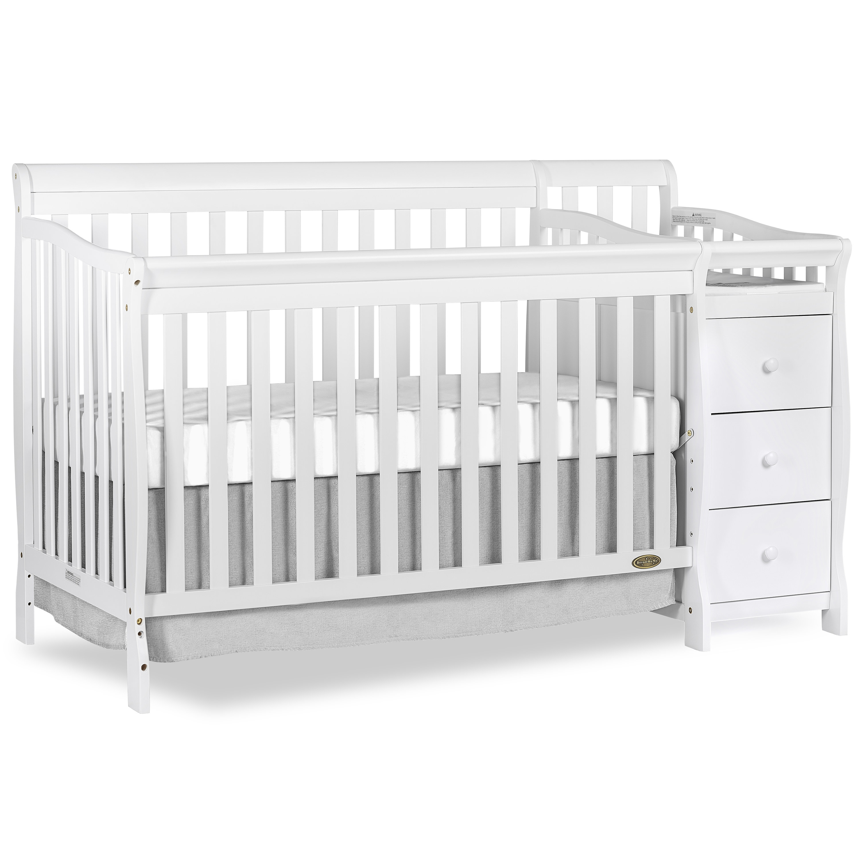 a white convertible crib with a changing table and drawers on the side