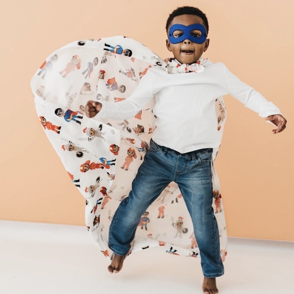Child wearing cape with images of little kids in imaginative outfits