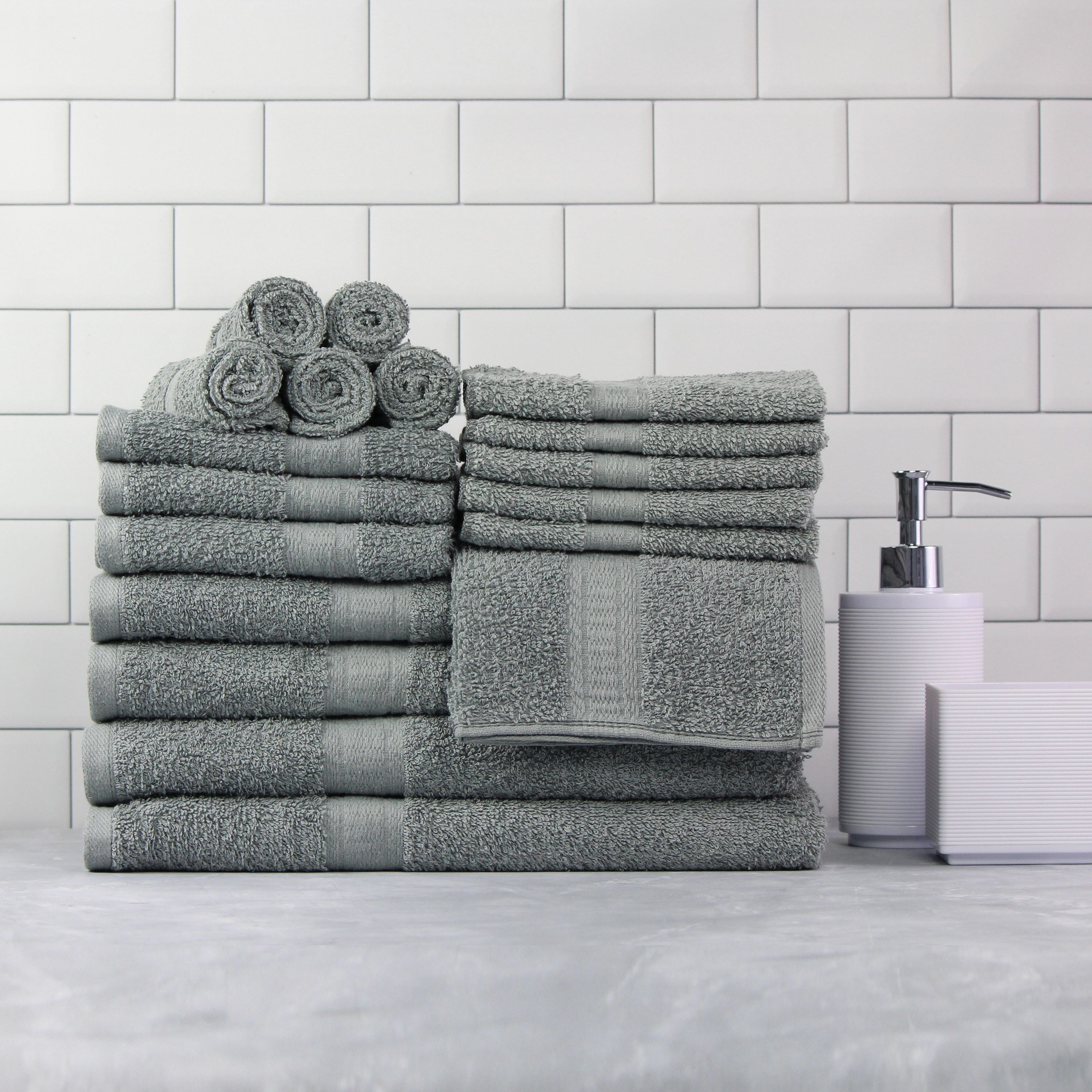 18 gray towels folded up on an counter