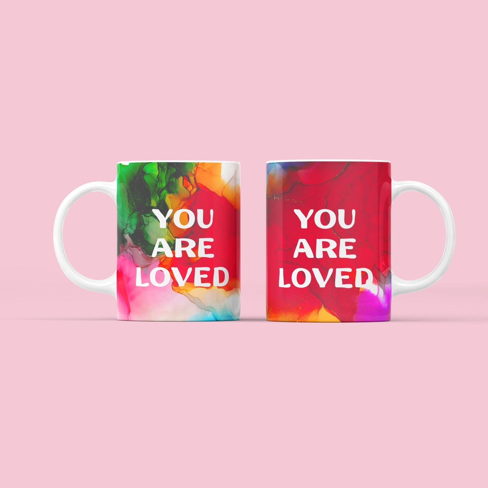 """a mug with a watercolor painting style with the words """"You are loved"""" in white on top"""