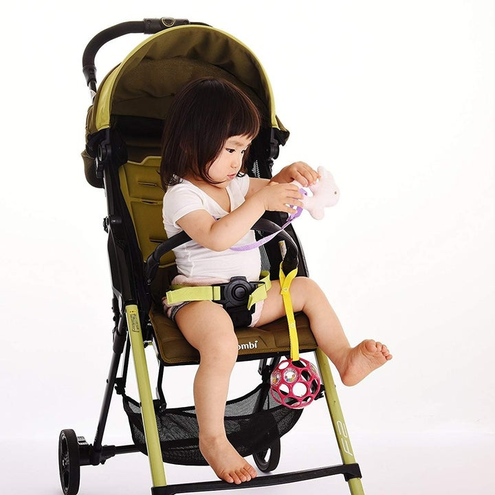 Child playing with toy while another is hanging from their stroller, not falling thanks to the strap it's attached to