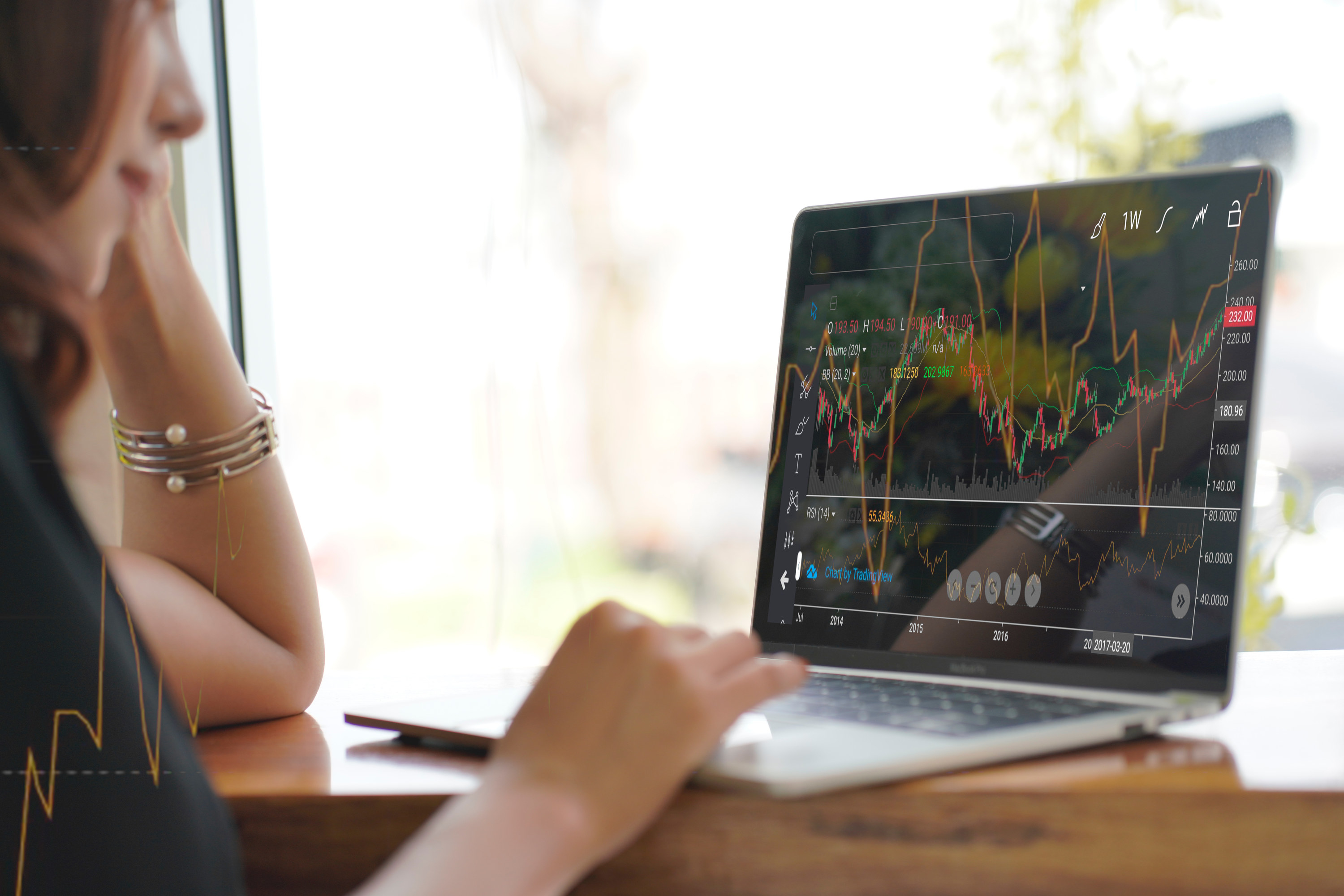 Woman looking at stock charts on a laptop