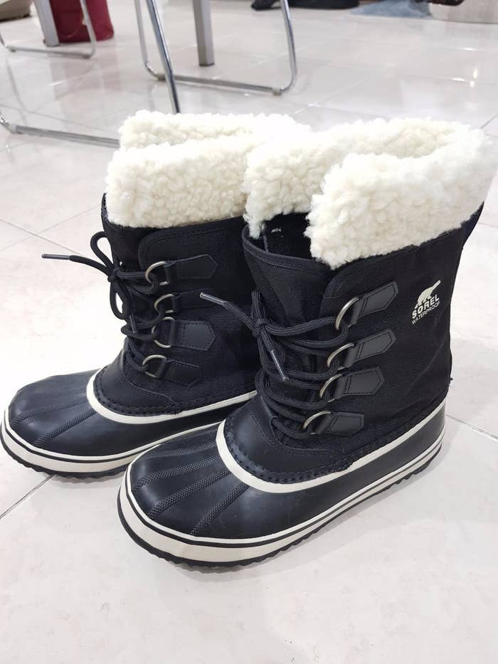 reviewer image of the tall boots with tie-up front, rubber soles, and footbed and faux fur on the top