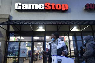 A man wearing a face mask leaves a Game Stop store with the a PlayStation box