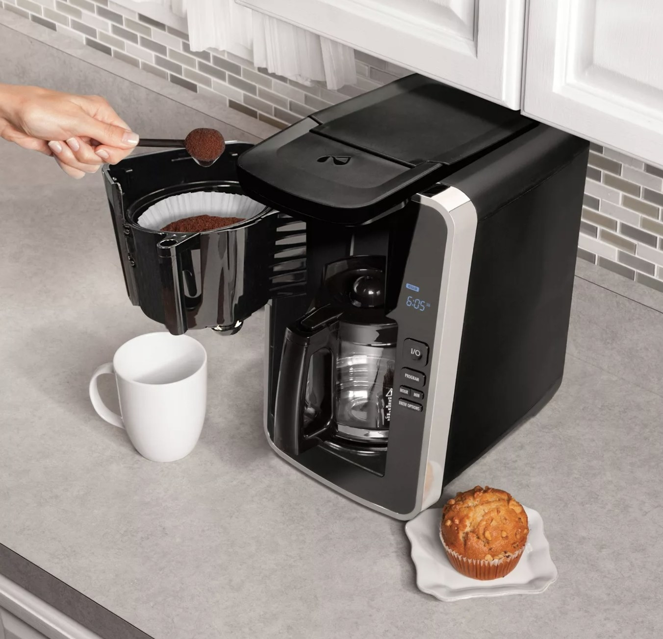 Person is pouring coffee into the coffee filter port in the coffee maker