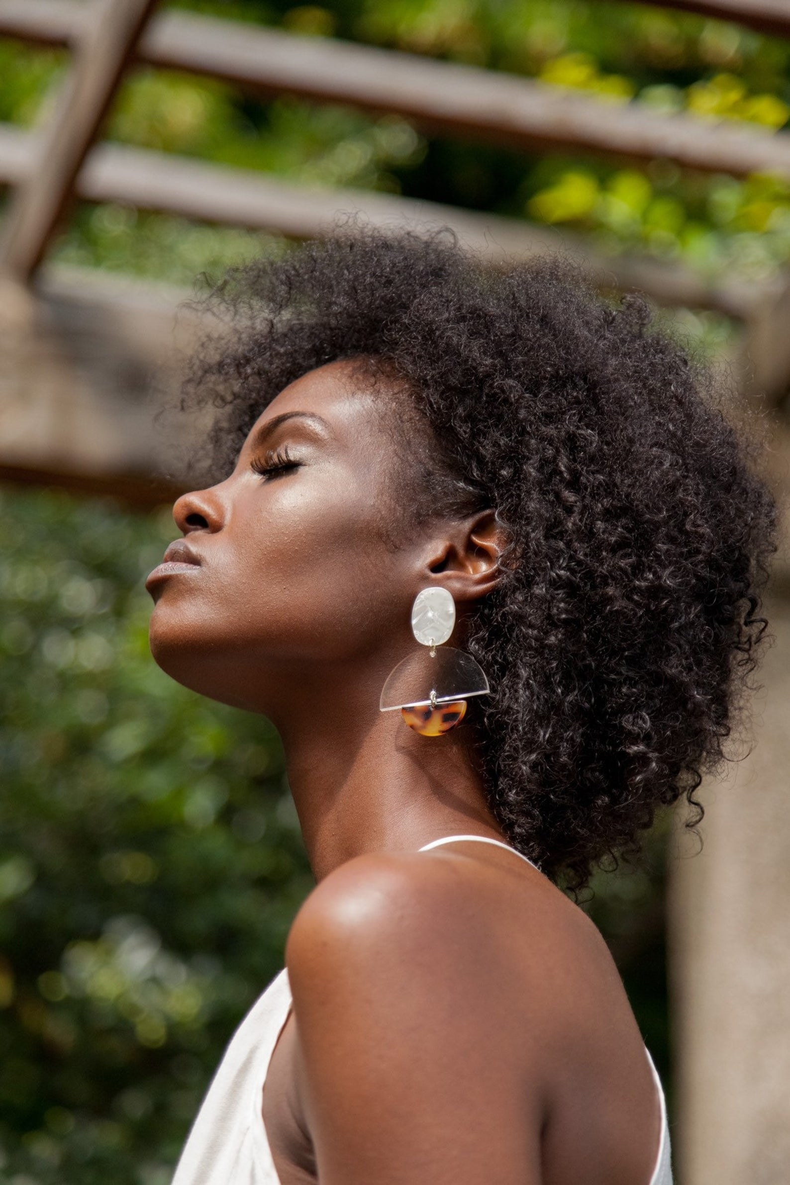 model wearing dangling earrings with one circular ivory portion, a clear half circle hanging underneath, and a smaller tortoiseshell half-circle underneath that