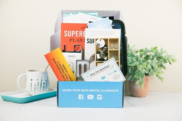 a Muse box with a coffee cup, books, pens, and other items in the box