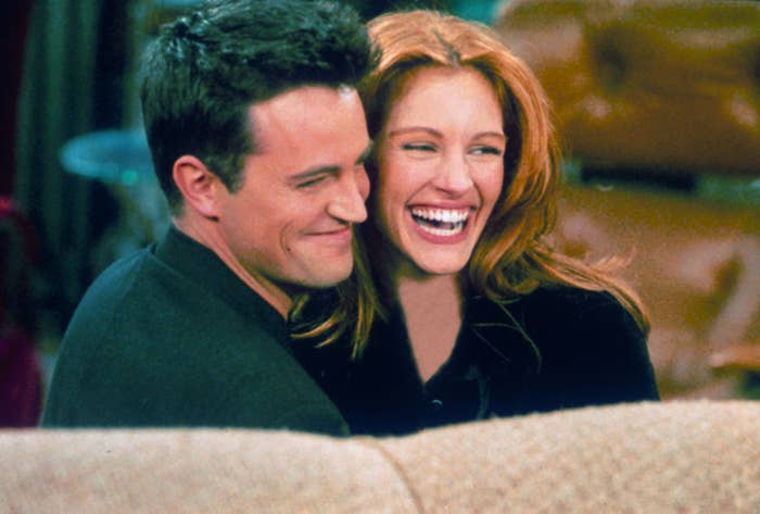 """Matthew Perry and actress Julia Roberts hug each other on the set of """"Friends."""""""
