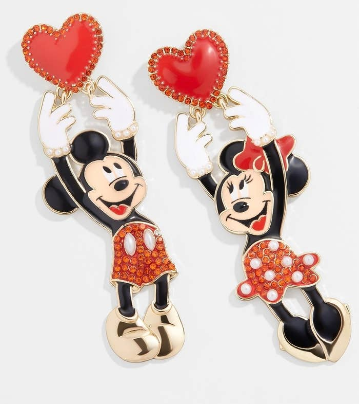 The rhinestone-embellished mismatched statement earrings, which are shaped like Mickey and Minnie each reaching up and grabbing a red heart