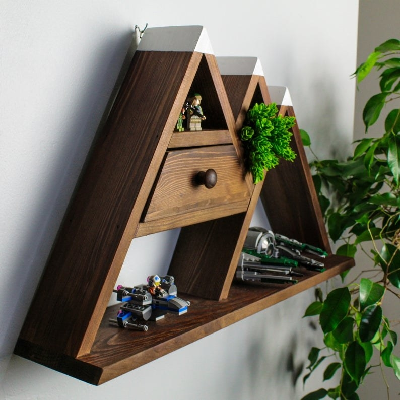 the wooden shelf with three triangles shaped like a mountain range and a drawer inside one of the triangles