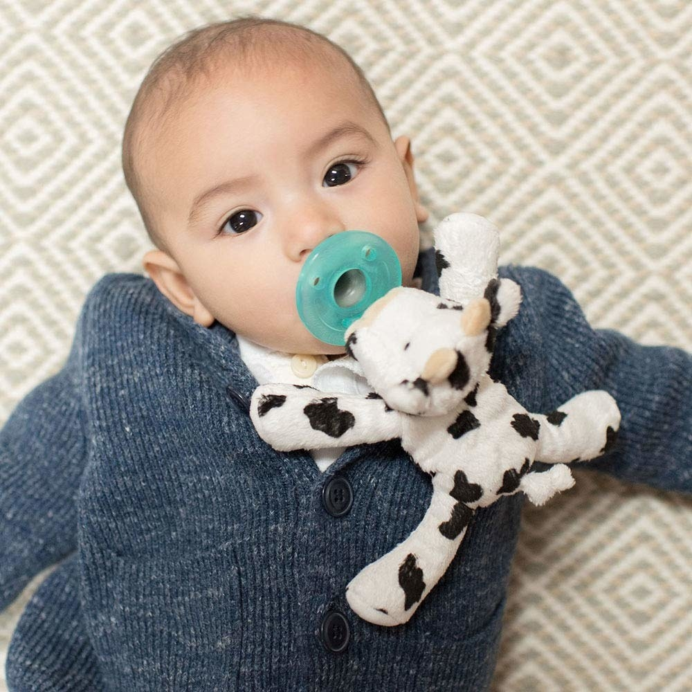 Infant with pacifier in mouth, attached to a small stuffed cow toy