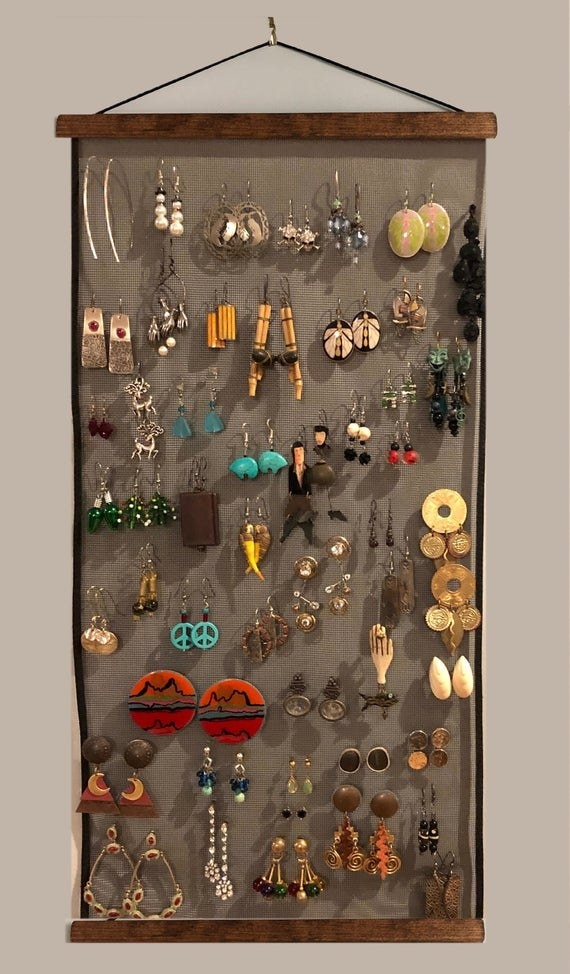 many pairs of earrings hanging on the wooden and mesh organizer