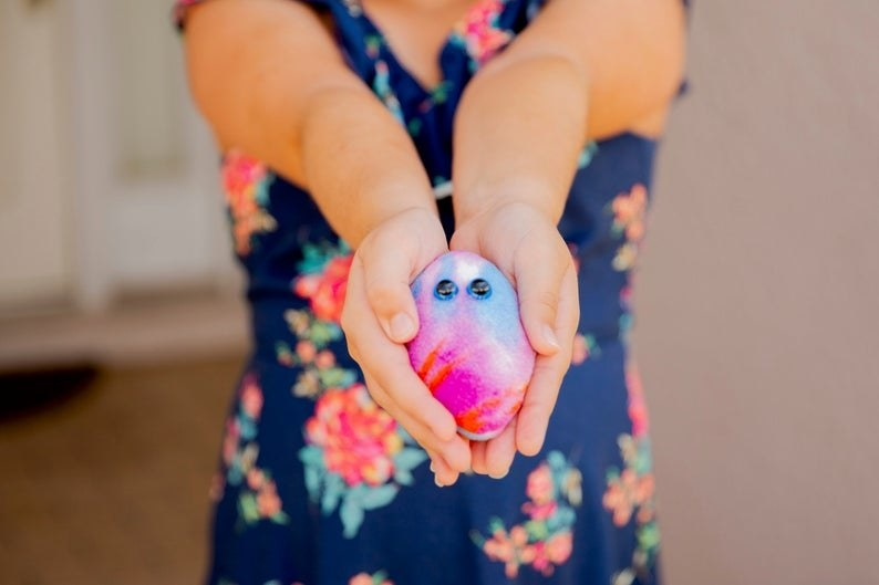 Pink, red, and blue Bother Buddy with cute google eyes in model's hands