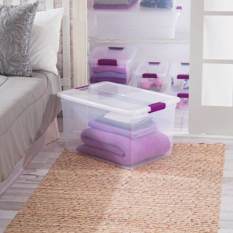 the clear bin with purple latches storing a blanket and sheet set in a bedroom