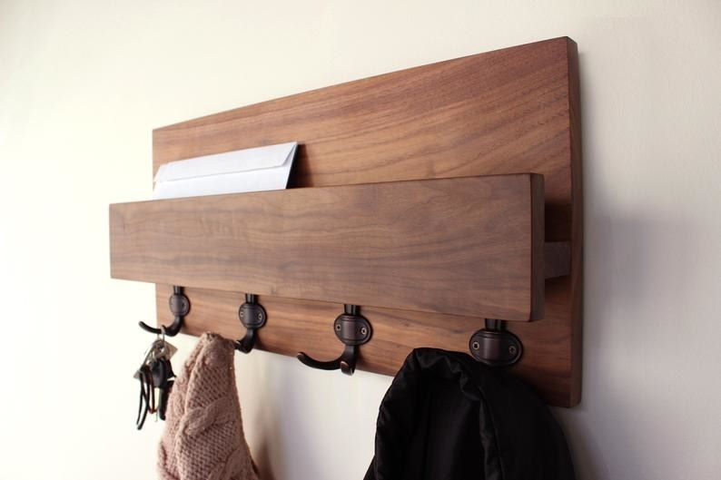 the brown shelf with four coat hooks hanging on the wall