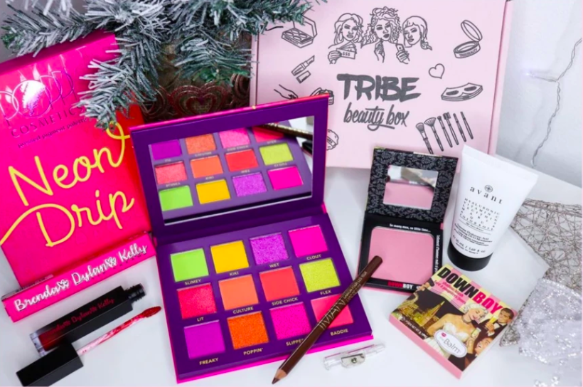 a Neon Drip eye palette, liquid lip, brown eyeliner pencil, and blush next to the beauty box