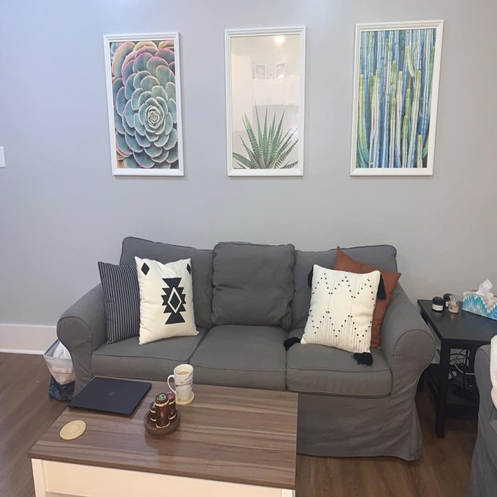three large art pieces hanging from a living room wall with command strips