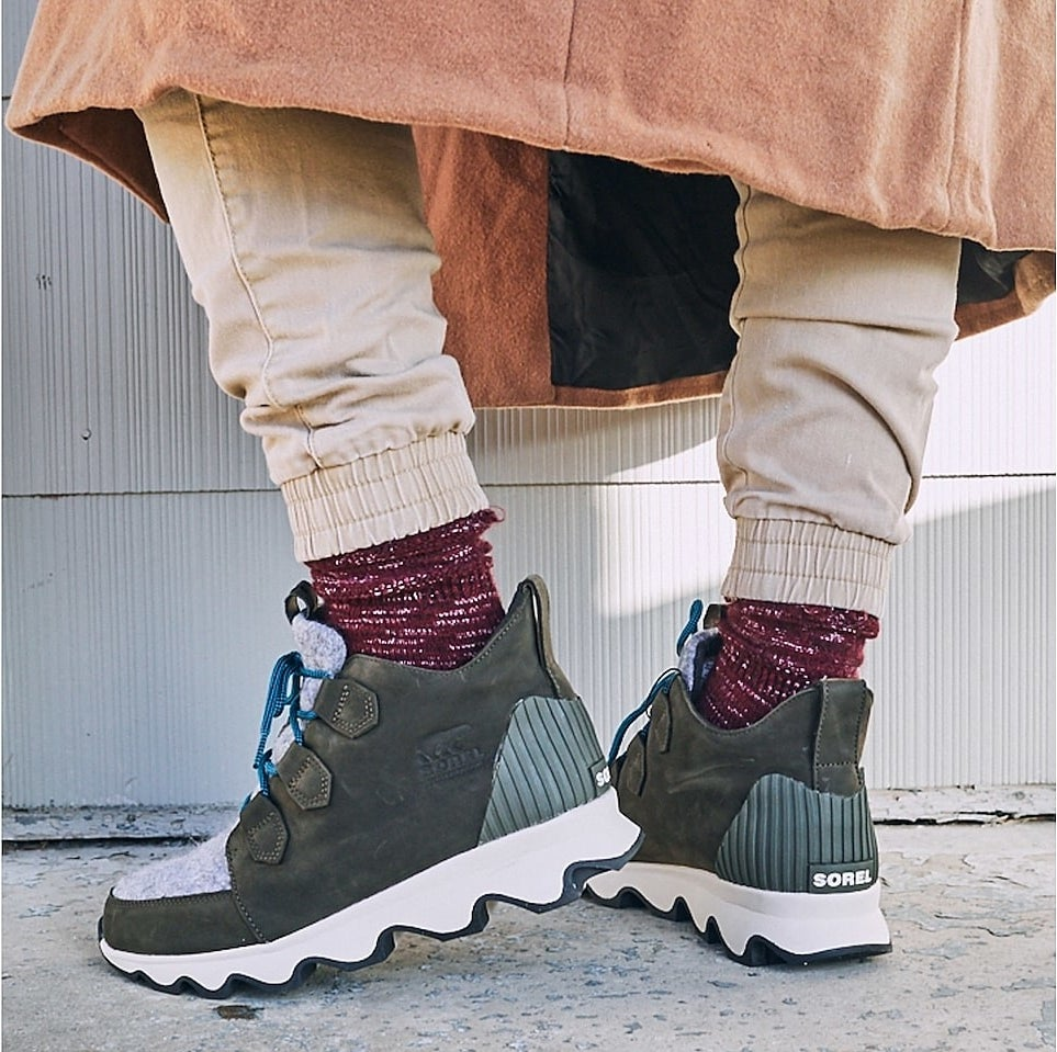 The sneaker-style shoe with white sole, olive green sides, light grey front, and blue laces