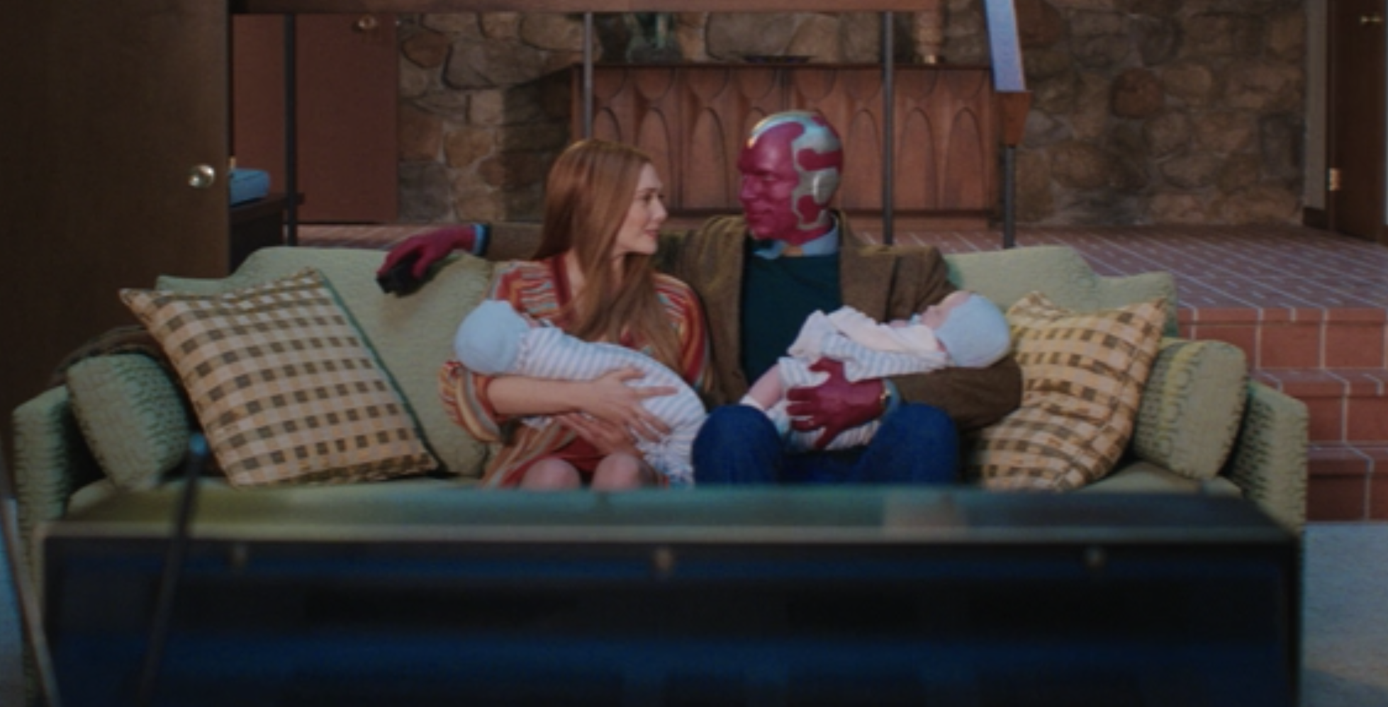 Vision and Wanda sitting on their couch holding their twin boys