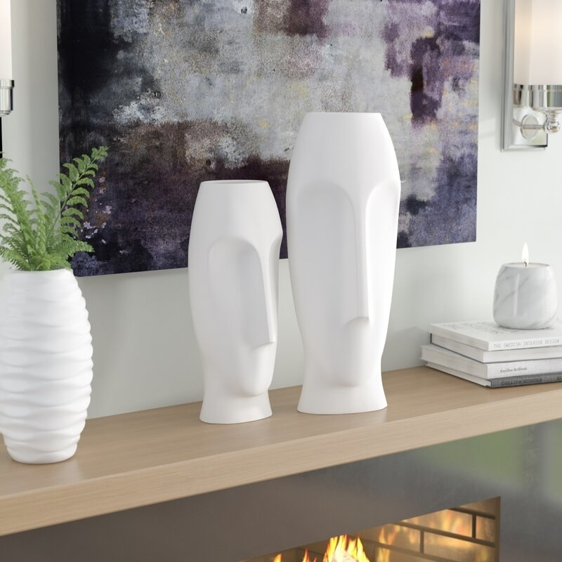 white face vases on a tan shelf with other white decor and a piece of gray and purple art