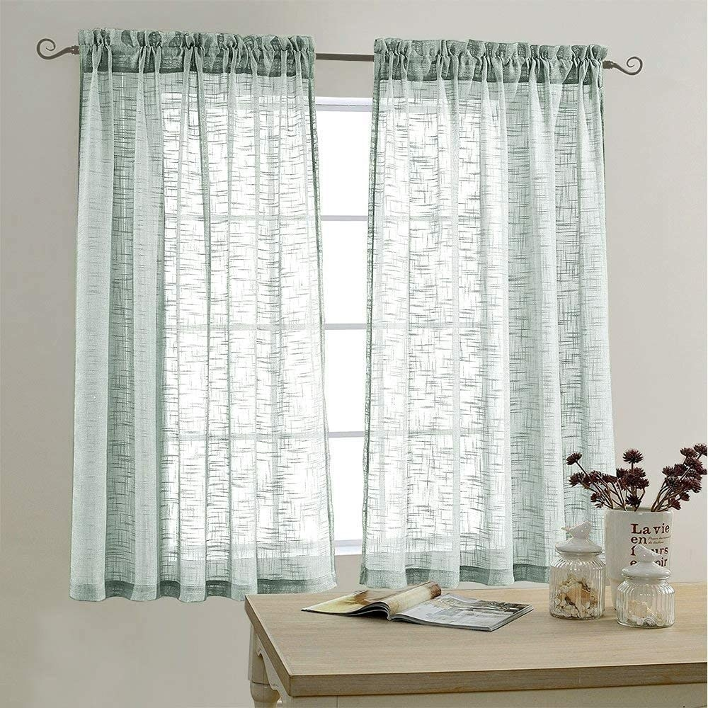 the sheer curtains in blue hanging in front of a window