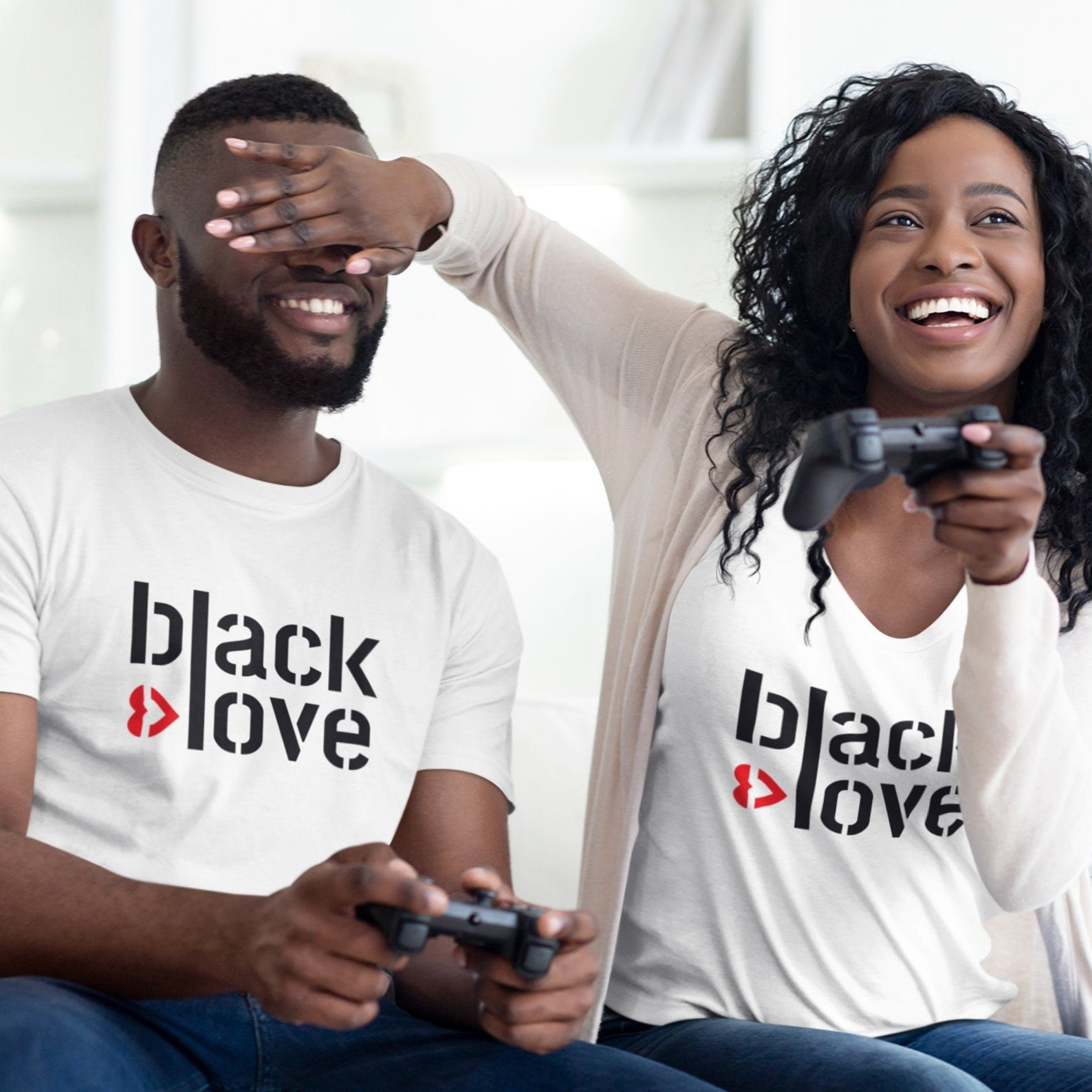a couple wearing white t-shirts that say black love on them. they're playing video games and she's covering his eyes with her hand.