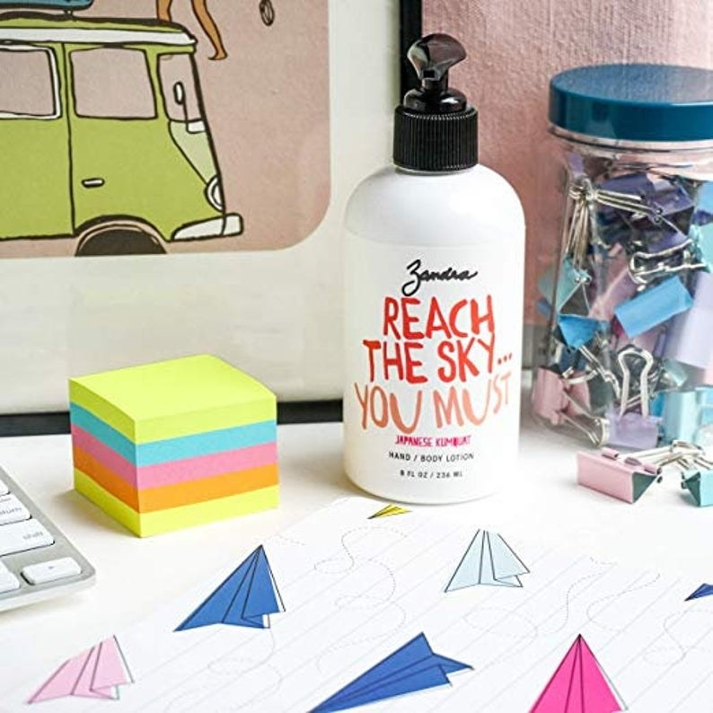 bottle of lotion sitting on a desk next to sticky notes and clips