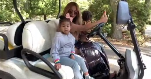 Rumi smiles while riding with her mom in a golf cart
