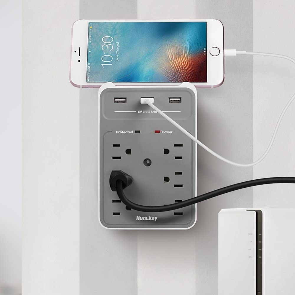 The charging port with six AC and thee USB outlets, with a cell phone charging while it rests on top of it