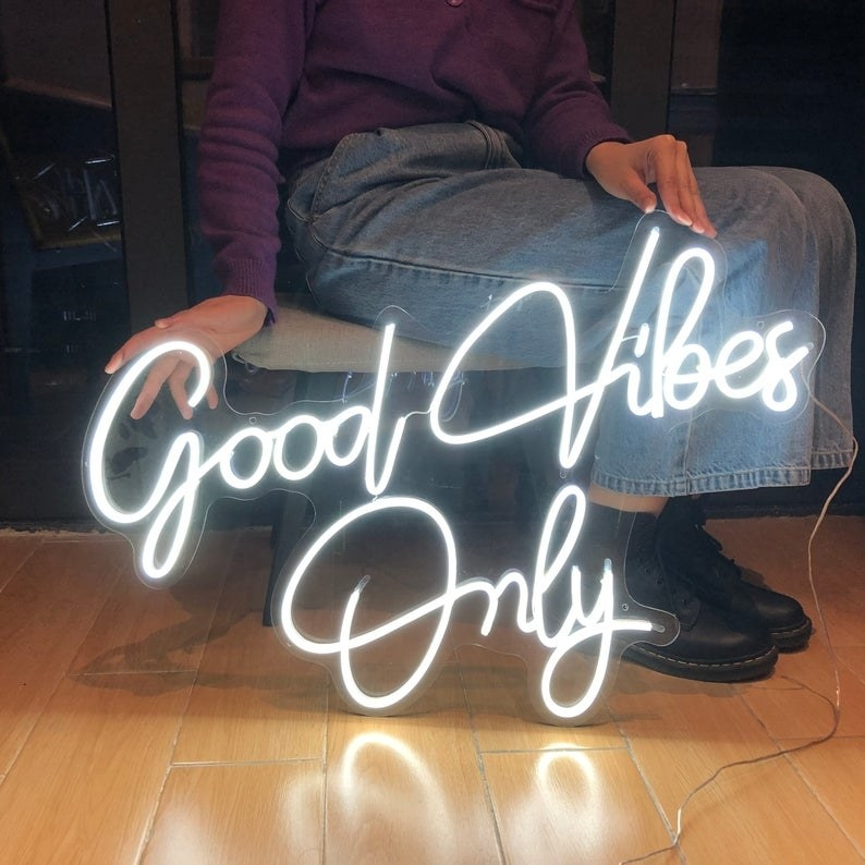"""a model sitting next to the white neon """"good vibes only"""" sign"""