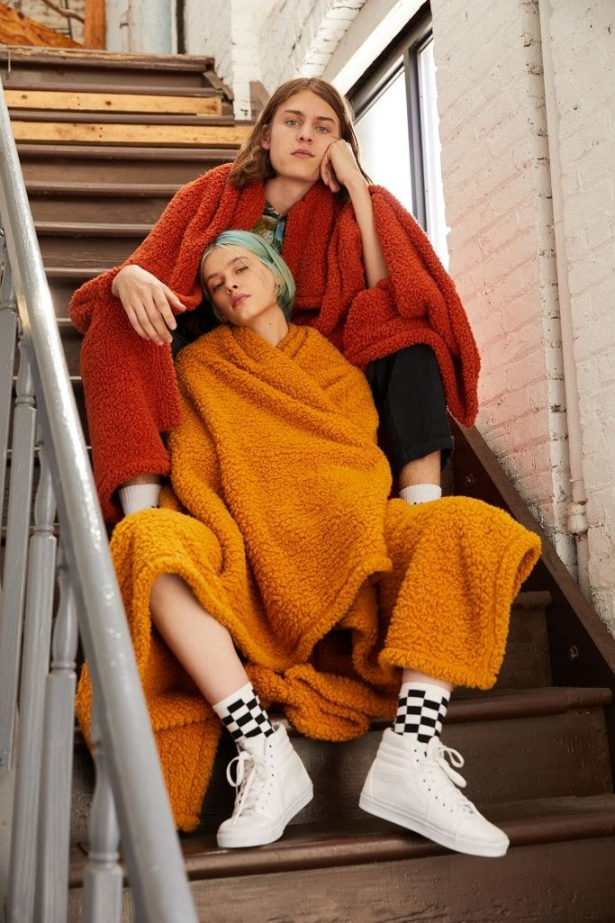 two models with a red and orange fuzzy blanket draped over their shoulders