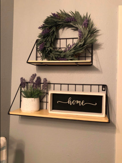 """a reviewer's photo of the two shelves hanging above each other holding a sign that says """"home"""" and a wreath"""