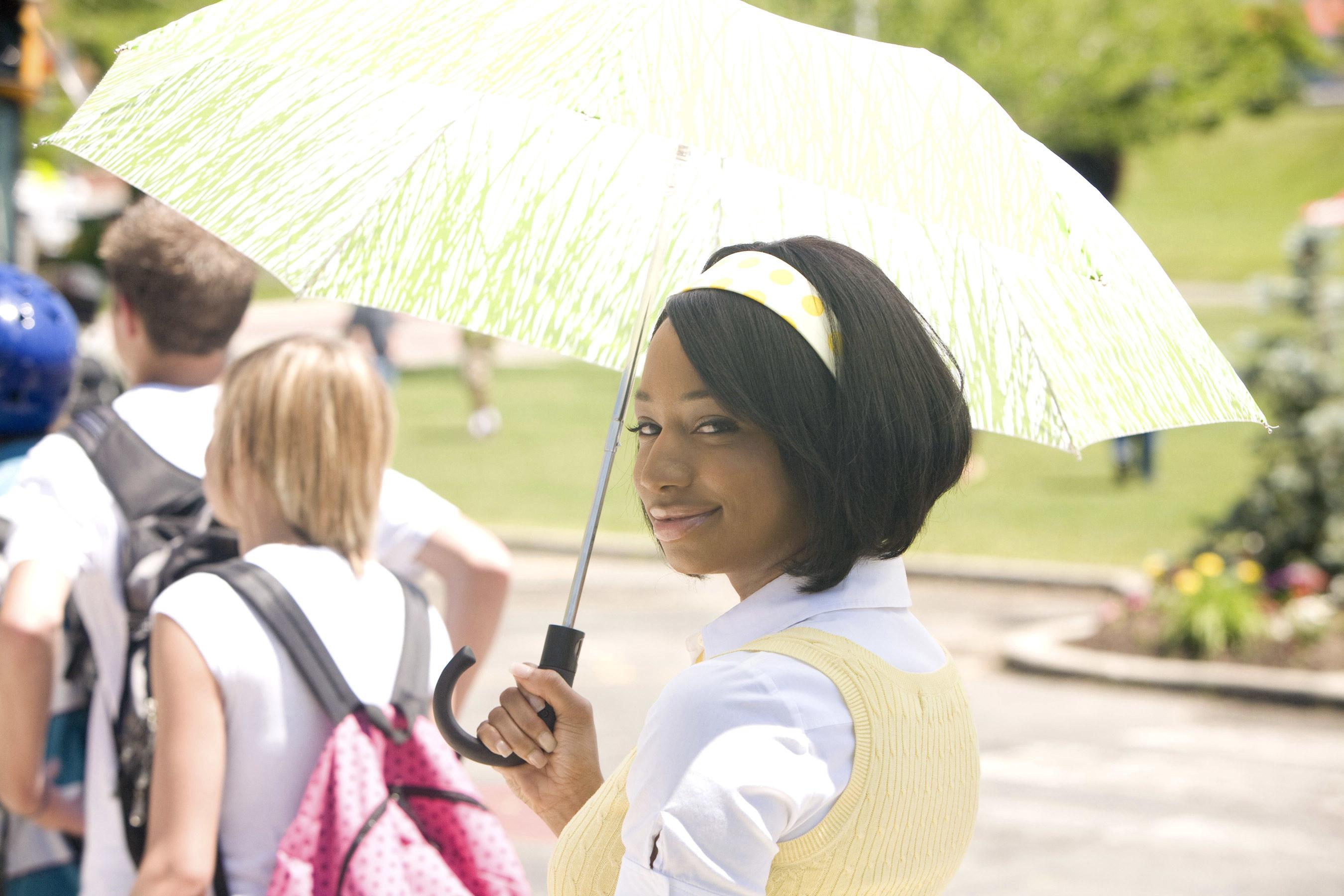 Taylor wearing a light yellow headband and holding a yellow umbrella