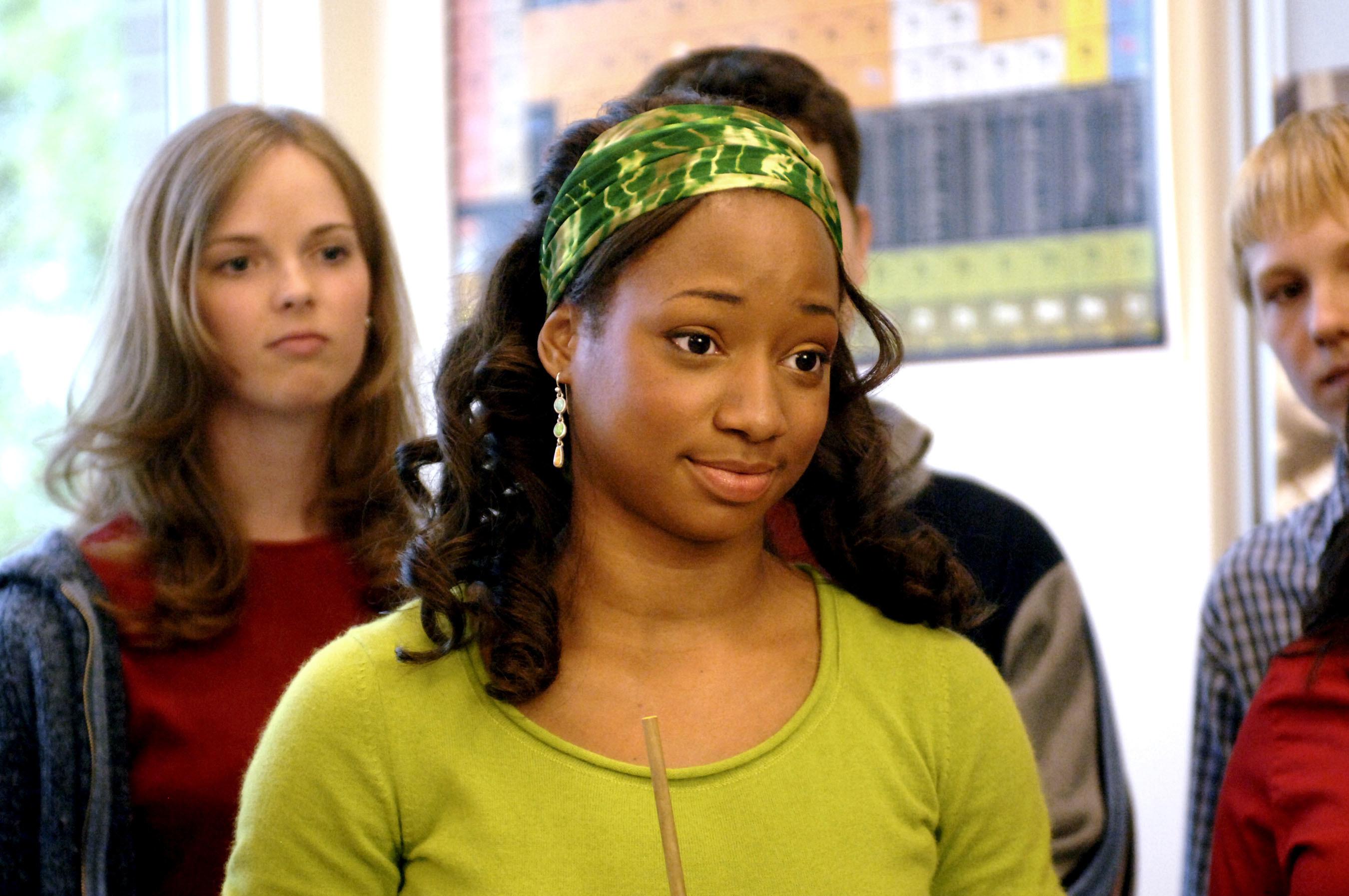 Monique as Taylor wearing a green headband