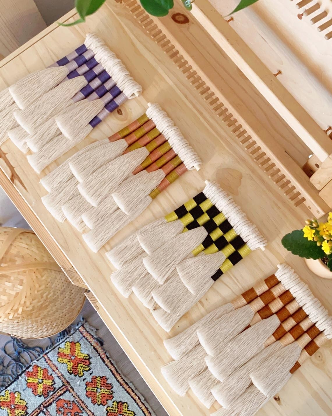 Four tassel wall hangings with checkered fiber pattern